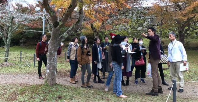 A group of tourists being guided through a Japanese garden in Izushi