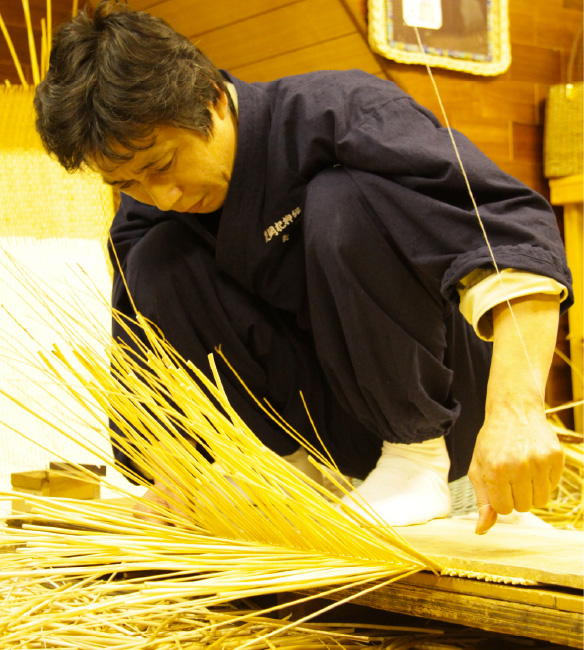 A man weaving wicker to make a bag