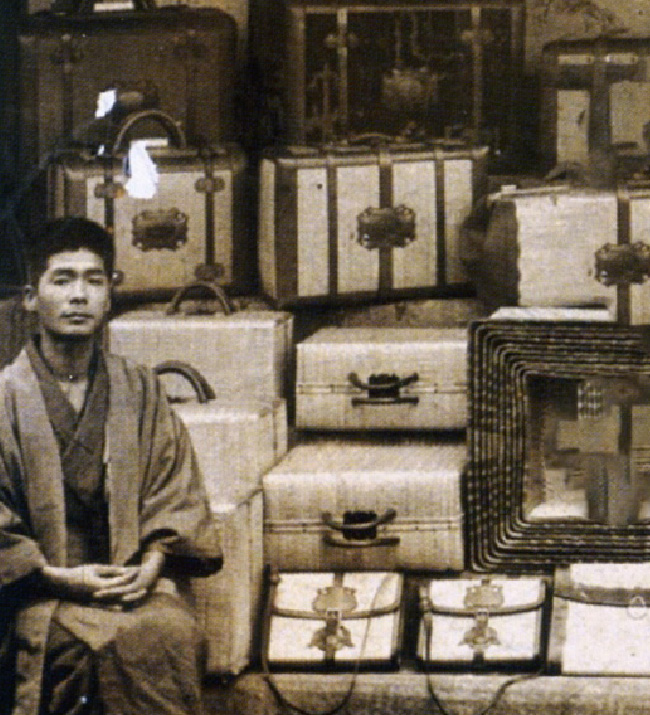 A man sitting next to a pile of Toyooka Kaban traditional wicker bags