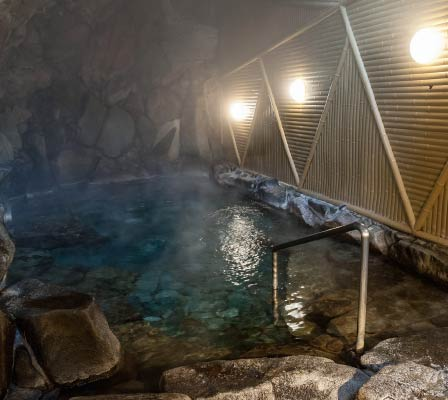 Ichinoyu Onsen's interior bath, surrounded by stones, gives the impression it is in a cave. It is filled with steam