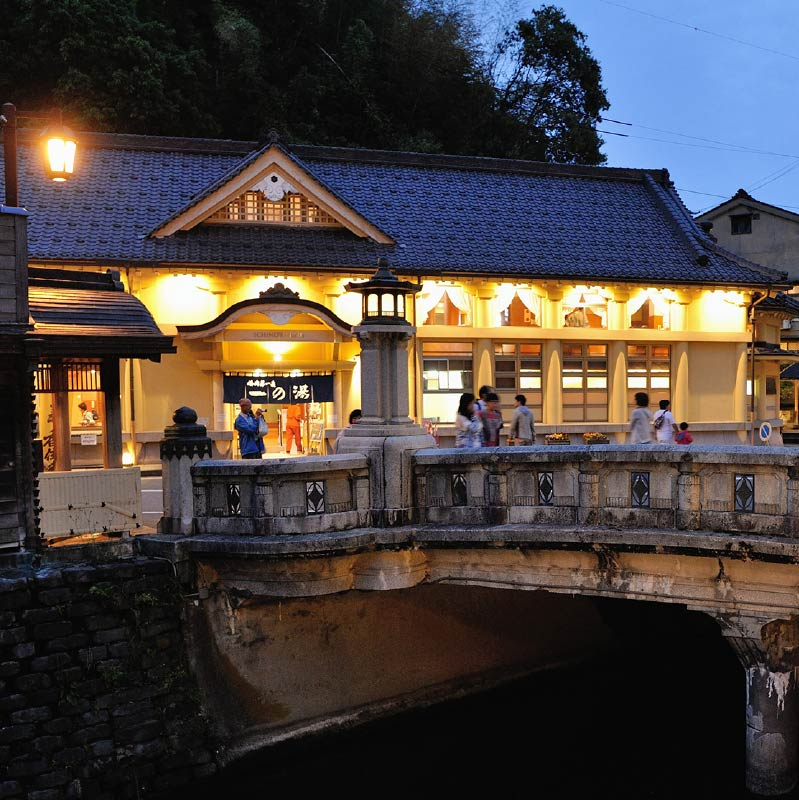 Ichinoyu Onsen's exterior. The large beige stone building, with it's black tiled roof is impressive