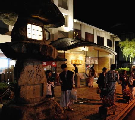 A large group of people in colorful yukata walking and talking around the entrance of Jizoyu Onsen
