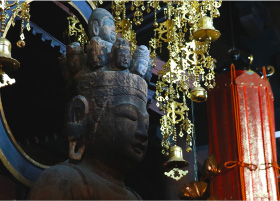 A closeup of a buddhist statue sitting inside the dark and atmoshperic Onsenji Temple