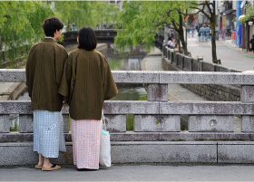 A couple looking over Kinosaki river, standing on a stone bridge