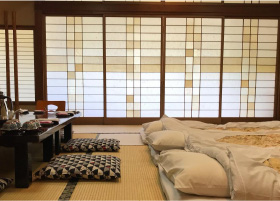 3 futons laying on the tatami floors of a ryokan room
