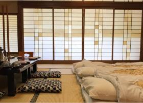 3 futons laying on the tatami floors of a ryokan room