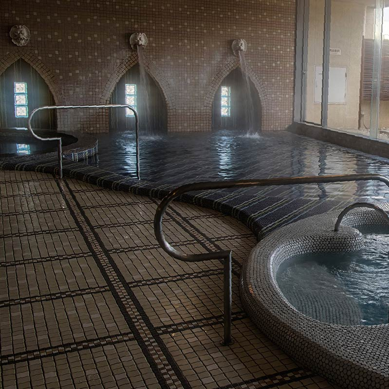 The modern tiled interior baths of Satonoyu Onsen at daytime. The decoration and ornamentation of the baths makes it seem almost gothic