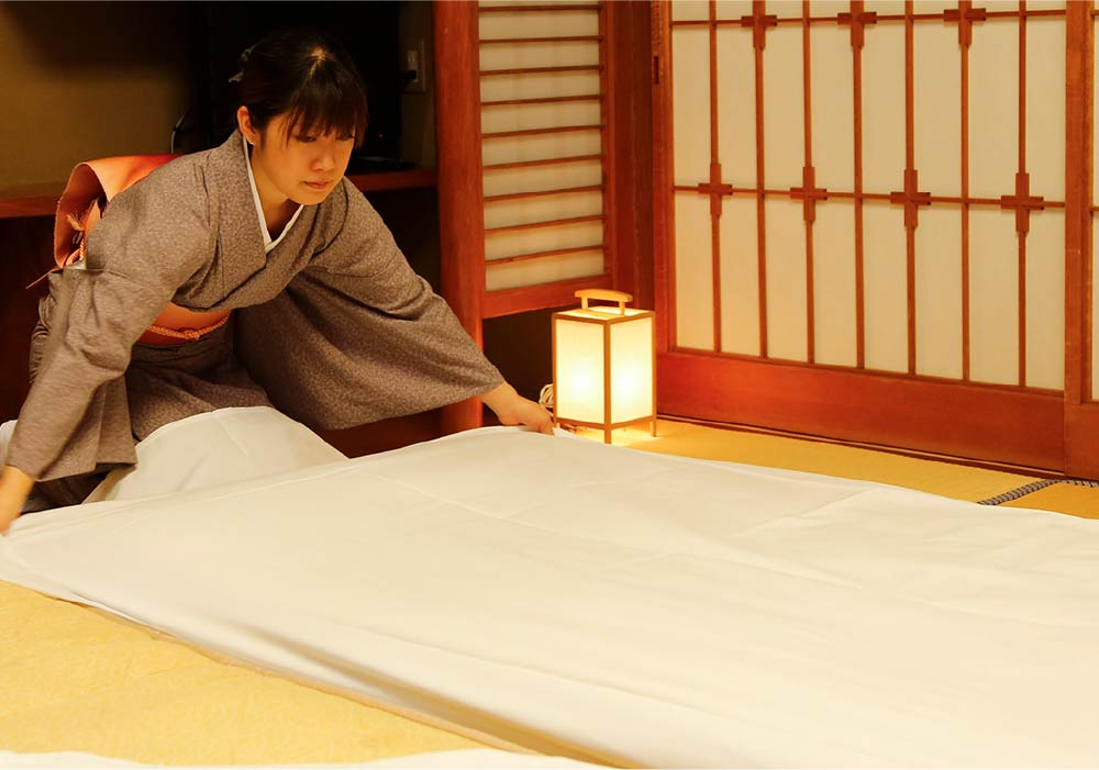 Ryokan staff setting up a futon for yet-to-arrive customers