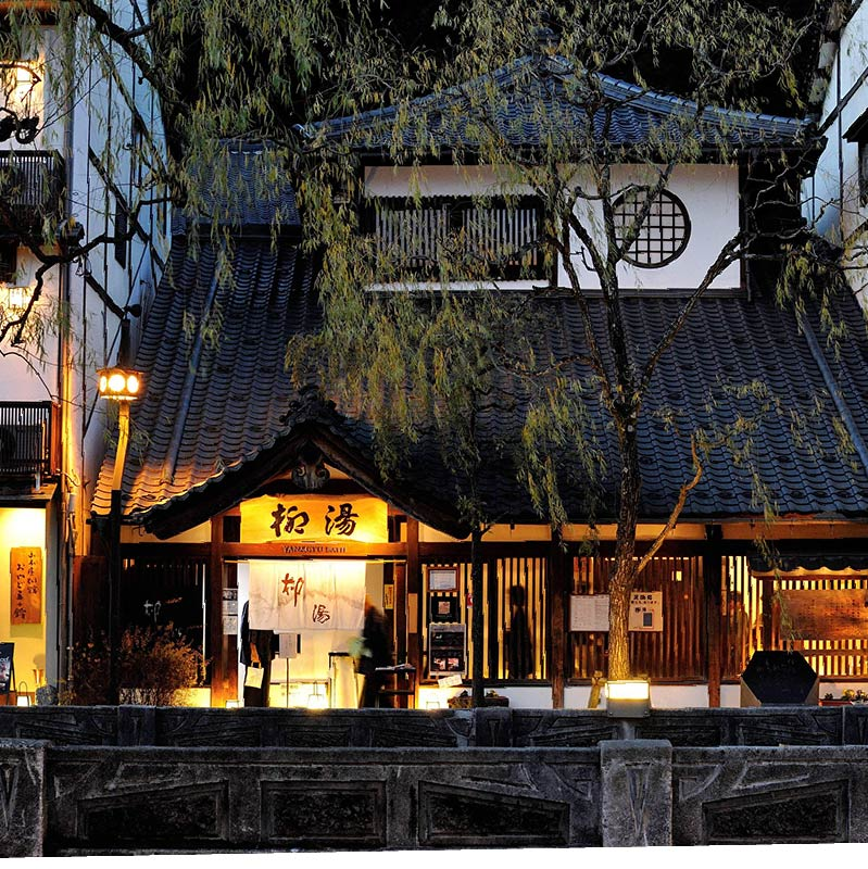 Yanagiyu Onsen exterior, moodily light at twilight with yellow lanters. A willow ('Yanagi' in Japanese) covers the entrance to the onsen.
