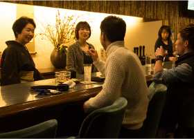 The 'mama-san' and other bartenders talking to the guests of the Snack Bar