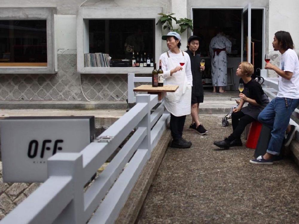 OFF Kinosaki – staff members sit outside on the bridge walkway enjoying some red wine and chatting