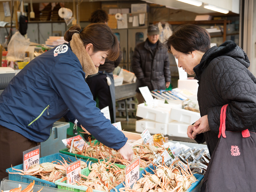 A shop clerk at a fishmarket selling crabs to a local lady