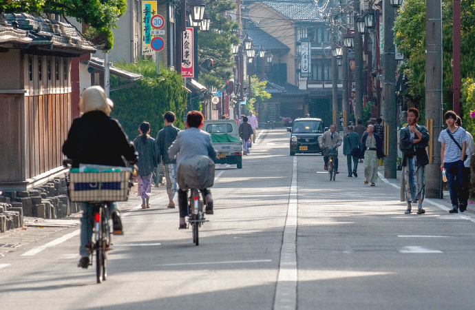 Various townspeople hustling and bustling on one of Kinosaki Onsen's many streets