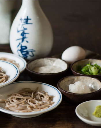 Izushi 'sara soba' soba noodles on plates, with diced spring onion and soy sauce in the shot.
