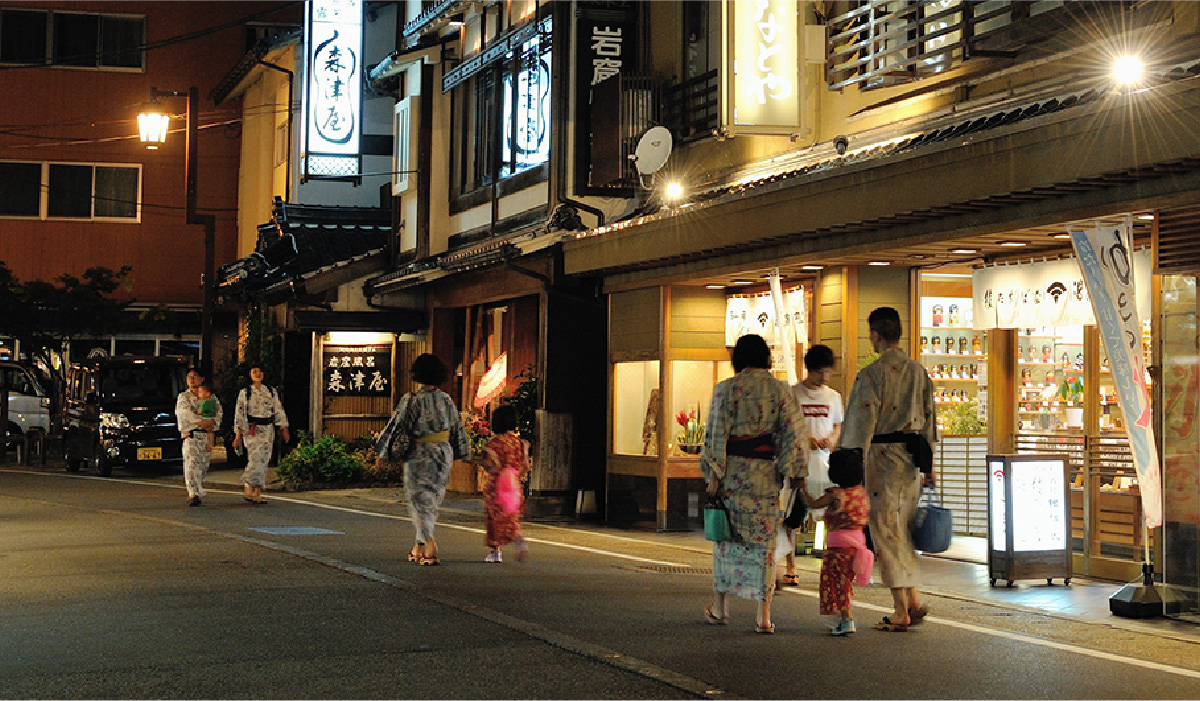 People in colorful Yukata walking the streets of Kinosaki Onsen at night