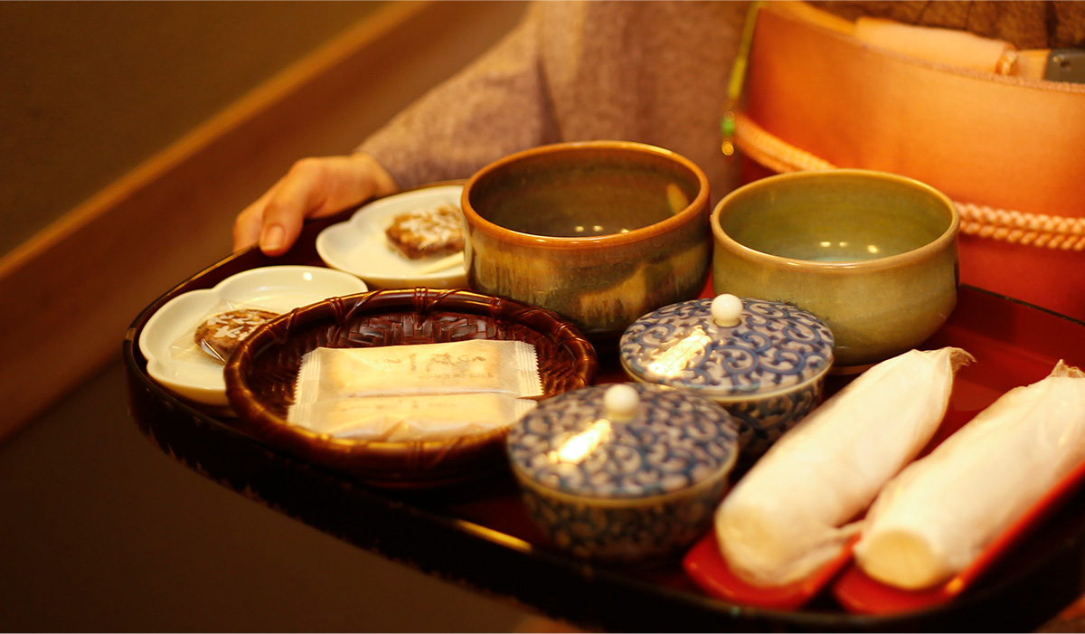 Ryokan staff taking a tray with tea, biscuits and hot napkins to a customer's room