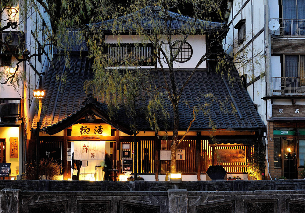 Yanagiyu Onsen's exterior at twilight. It's exterior lanterns give off a strong atmosphere